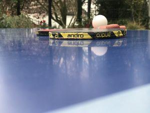 Zweit TT-Schläger und ein Ball liegen auf einer Outdoor-TT-Platte